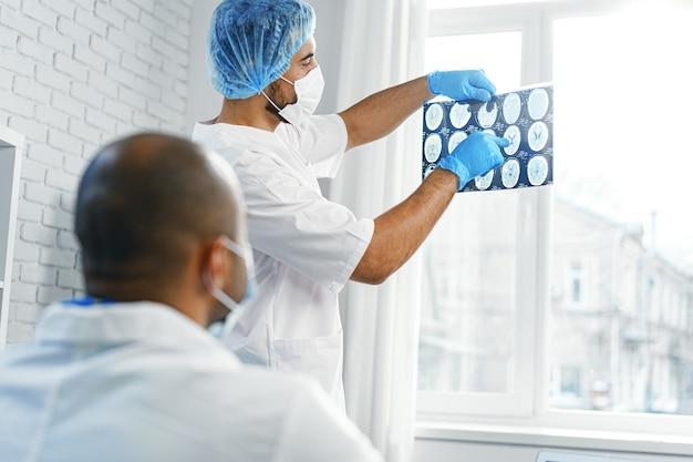 男性医師が病院のキャビネットで患者のmri脳スキャンを検査します