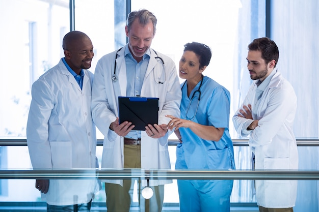 Male doctors and nurse having discussion over clipboard in corridor