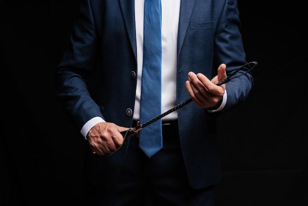 Доминирующий мужчина бизнесмен в костюме держит в руках кожаную плетку флоггер для доминирования в бдсм-сексе