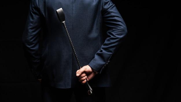 Доминанта мужского пола держит на спине кожаный хлыст
