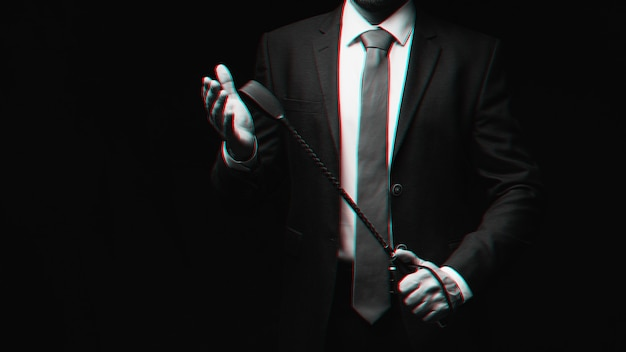 Male dominant holds a leather whip flogger for hard bdsm sex. black and white with 3d glitch virtual reality effect