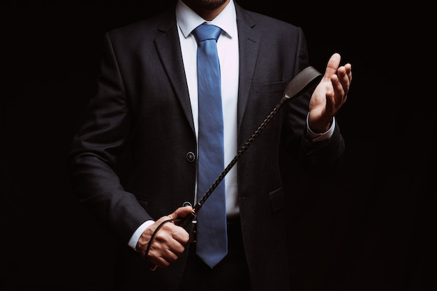 Male dominant holds a leather whip