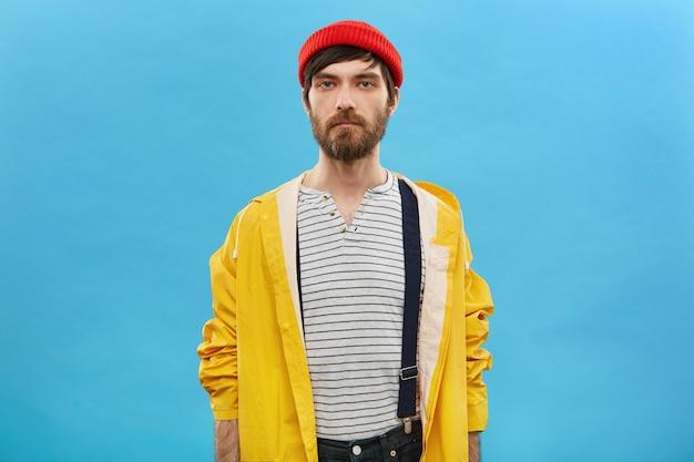 Мужчина, одетый в стильный головной убор и плащ, позирует на пустой синей стене студии
