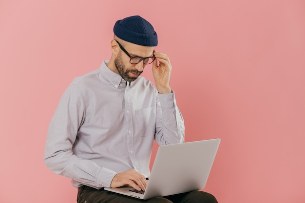 Male dressed in stylish clothes, works freelance, types information on laptop computer
