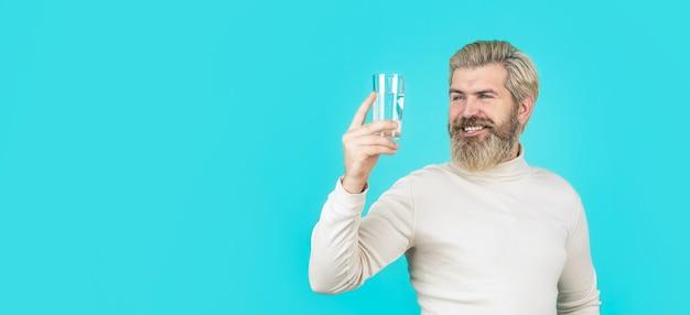 コップ一杯の水から飲む男性。ヘルスケアのコンセプト、ライフスタイル、クローズアップ。彼女の手に透明なガラスを持って笑顔の男性。幸せなひげの男は水を飲みます。