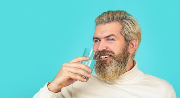 コップ一杯の水から飲む男性