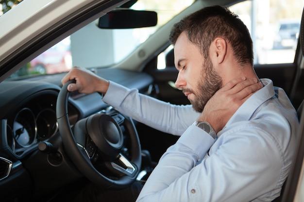 Мужчина водитель с болью в шее, сидя в своей машине
