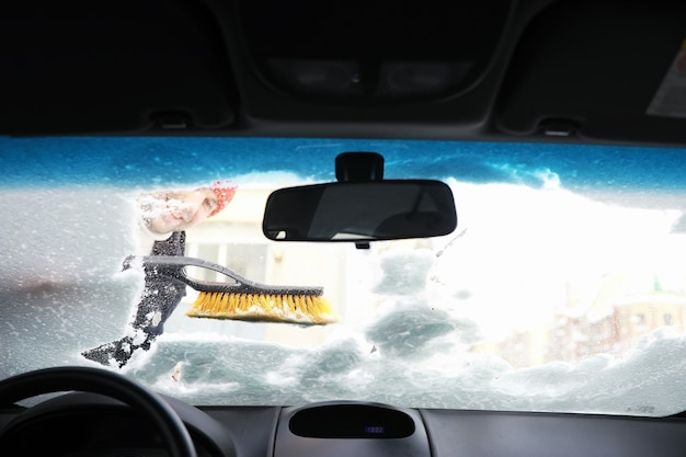 A male driver is standing in front of a car the owner cleans the car from snow in winter car after