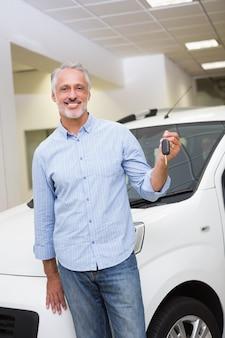 Мужской водитель показывает ключ после того, как новый автомобиль