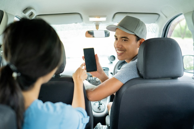 Male driver shows his smartphone to approve the payment