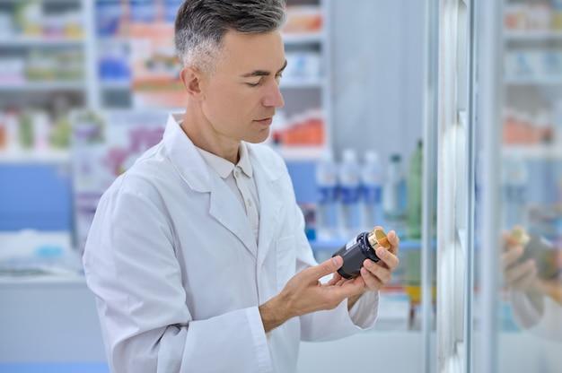 약국 진열장 옆에 서 있는 손에 건강 보조 식품을 들고 있는 남성 약사