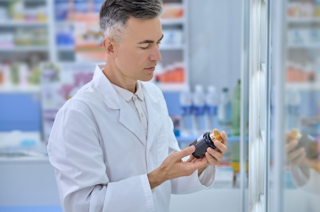 Male druggist with a dietary supplement in his hands standing beside the drugstore display cabinet