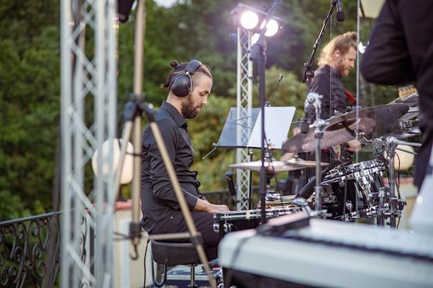 Male drummer having concert rehearsal on the street
