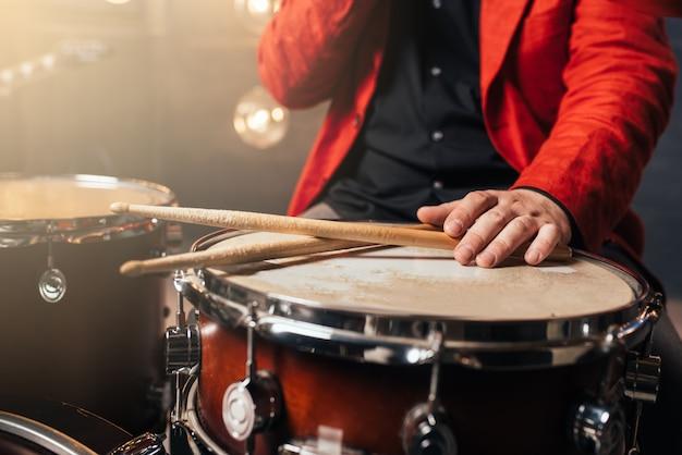 Барабанщик в красном костюме сидит за барабанной установкой.