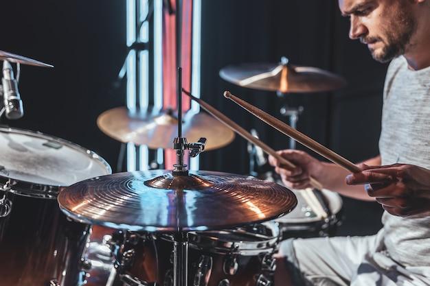Un batterista maschio che suona la batteria in una stanza buia con una bella illuminazione.