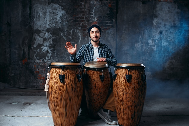Male drummer playing on wooden bongo drums in factory shop