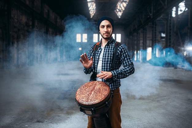 Male drummer playing on wooden drum
