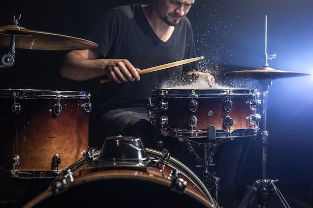A male drummer plays drum sticks on a snare drum with splashing water in a dark room.