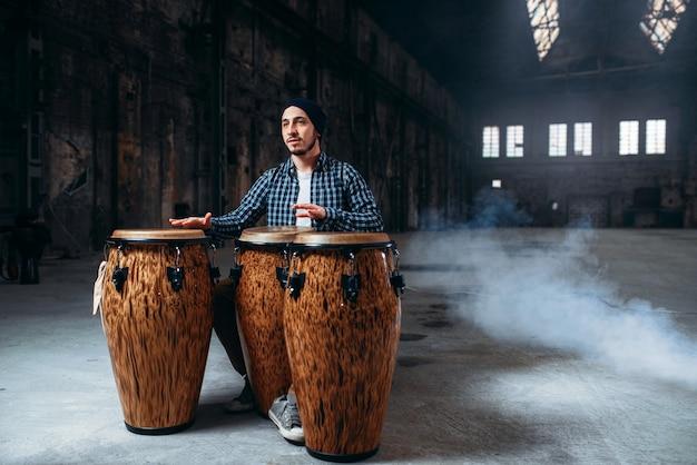 男性ドラマーはファクトリーショップで木製ドラムを果たしています。
