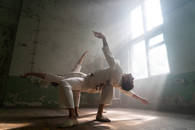 Male duo making acrobatic tricks wearing costume of insane people in abandoned room with sun rays from windows.