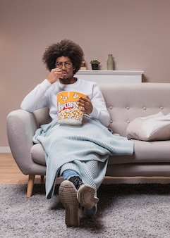 Male eating popcorn on couch