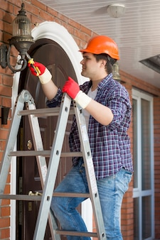 Male electrician in hardhat standing stepladder and repairing lamp on house outdoor wall