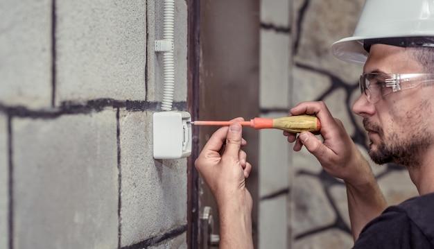 Мужской электрик-техник, подключает оборудование с помощью инструмента