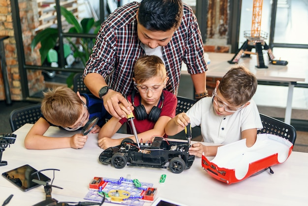Мужской инженер-электроник с европейскими школьниками работая в умной школьной лаборатории и испытывая модель радиоуправляемого электрического автомобиля.