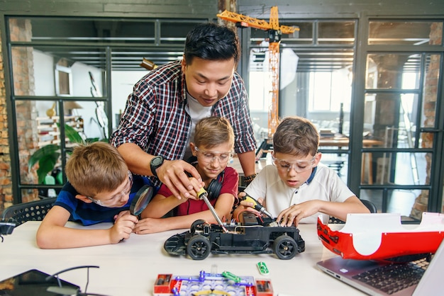 Male electronic engineer with european school children working in smart school lab and testing model of radio controlled electric car.