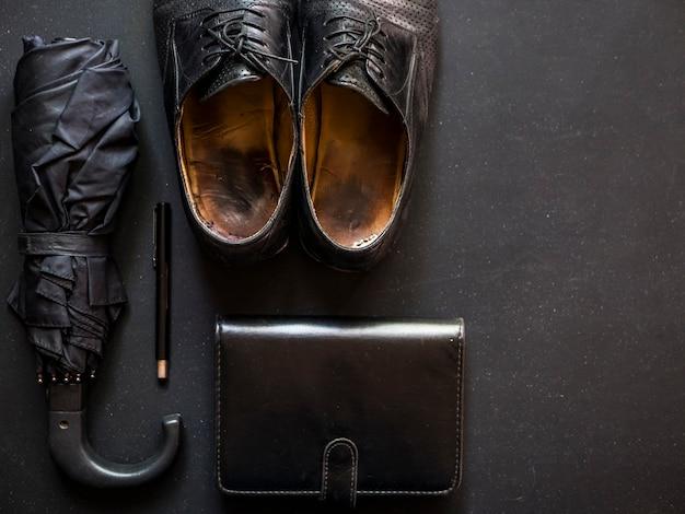 Male elegant trendy businessman supplies umbrella shoes notebook and pen copy space
