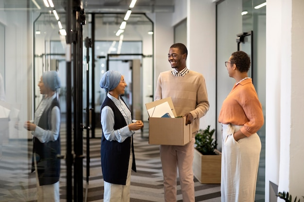 Impiegato maschio che esplora il suo nuovo posto di lavoro in ufficio mentre trasporta una scatola di effetti personali