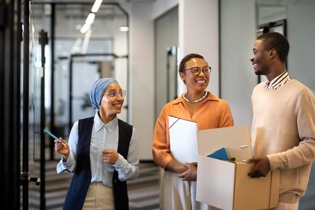 Сотрудник-мужчина исследует свое новое место работы в офисе, неся коробку с вещами