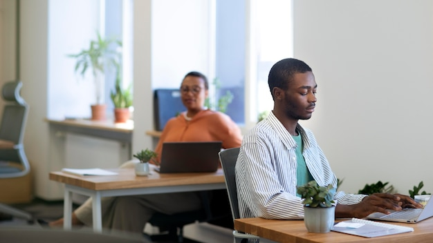 Male employee getting used to his new office job while working on laptop at desk