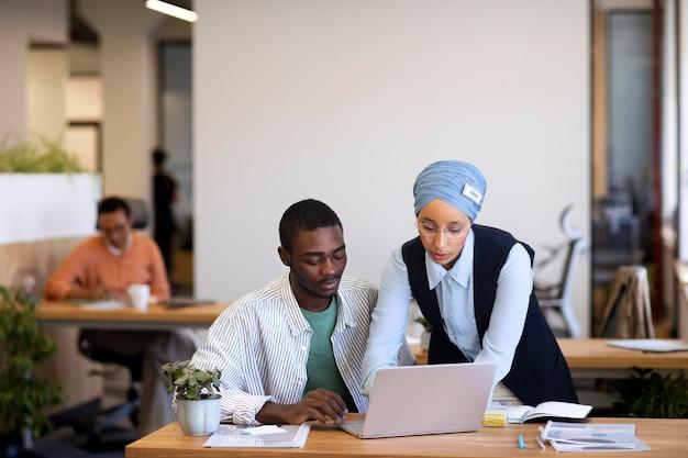 Сотрудник-мужчина привыкает к своей новой офисной работе вместе с коллегами-женщинами