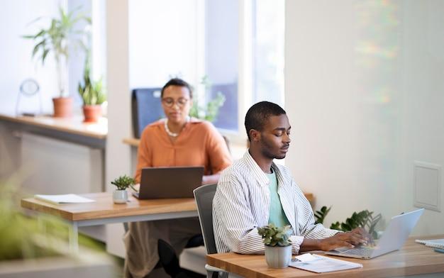 Сотрудник мужского пола привыкает к своей новой офисной работе, работая на ноутбуке за столом