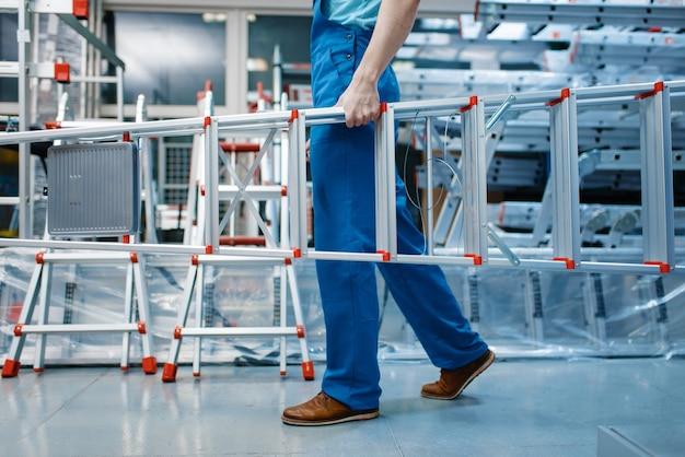 제복을 입은 남성 직원이 도구 저장소에 새로운 알루미늄 접사 다리를 들고 있습니다. 사다리가있는 부서, 하드웨어 상점의 장비 선택, 악기 슈퍼마켓