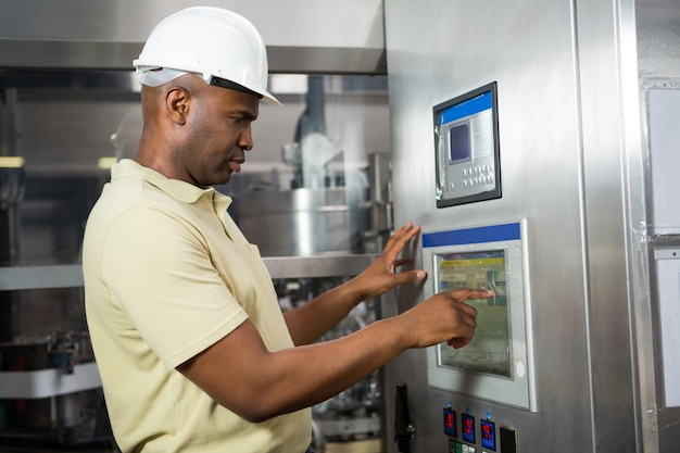 Male employee operating machine in manufacturing industry