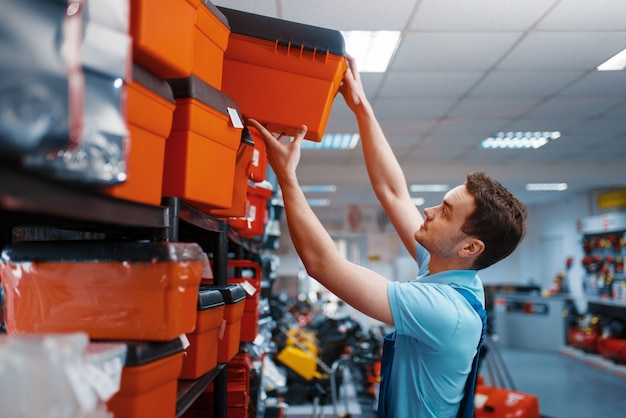 Male employee in uniform choosing toolbox in tool store. choice of professional equipment in hardware shop, instrument supermarket