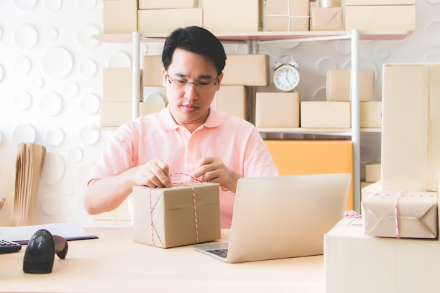 The male employee was tying the rope that the customer ordered for tightness after packing the goods in order to deliver to the carrier for delivery.