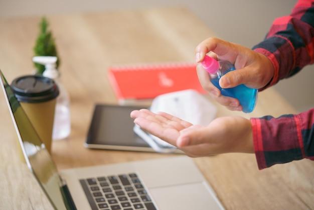 男性従業員ヘルスケアコロナウイルスcovid-19感染を防ぐためにアルコールジェルで手を洗うマスクを着用、在宅勤務のコンセプト