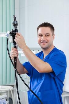 男性の内視鏡医は患者を受け入れる準備をしています