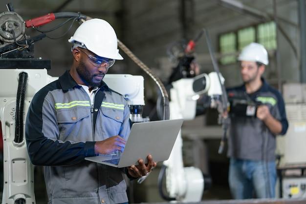 工場でラップトップを備えた男性エンジニアのチェックと検査制御ロボットアーム溶接機