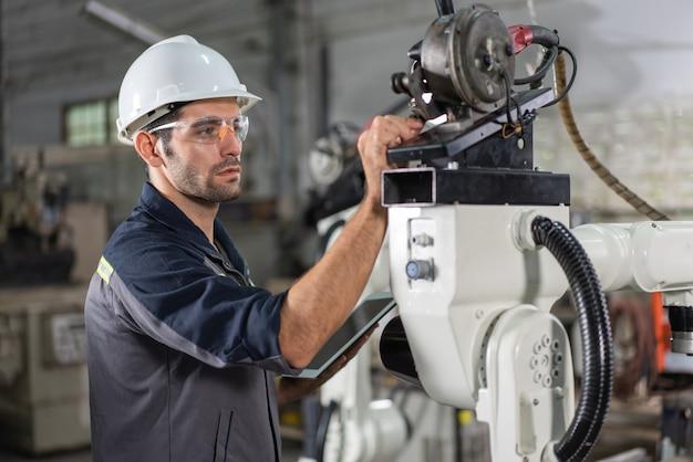 工場でタブレットを備えた男性エンジニアのチェックと検査制御ロボットアーム溶接機