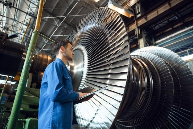 Инженер-мужчина проверяет лопатки рабочего колеса турбины на заводе