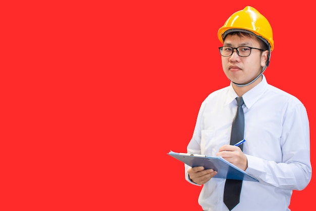 Male engineer finger pointing in factory with note on notepad