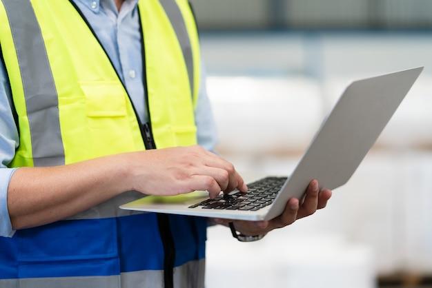 Рука мужского инженера, использующая ноутбук, проверяя продукт на складской фабрике