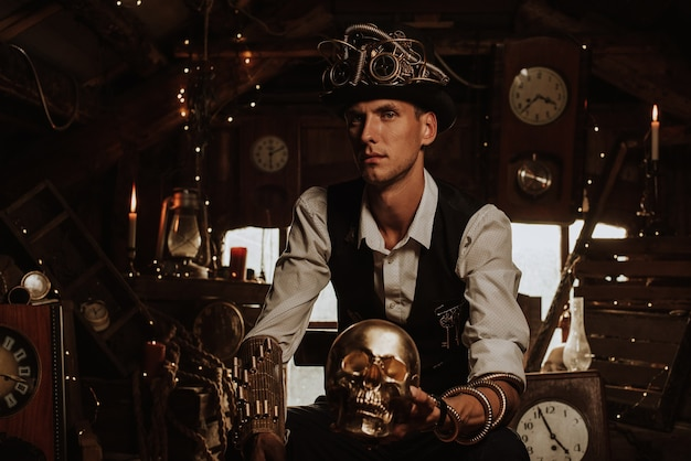 Мужчина-инженер в костюме стимпанк в шляпе-цилиндре с очками и механизмами