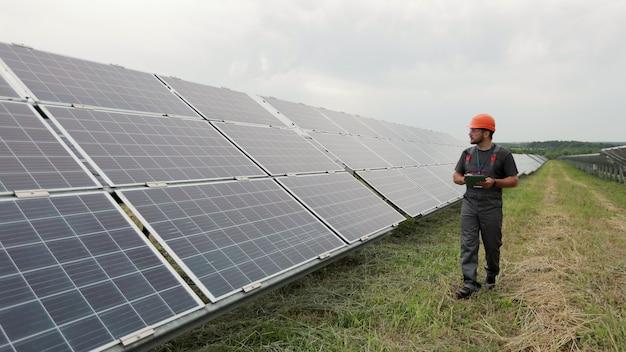 안전모를 쓴 남성 엔지니어가 디지털 태블릿을 들고 태양광 패널 설치를 확인하는 재생 에너지 스테이션을 걷고 있습니다. 대체 에너지. 청정 에너지 개념입니다.
