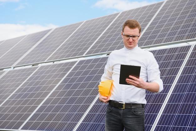 Инженер-мужчина в шлеме с планшетом в руках, стоя возле солнечных батарей