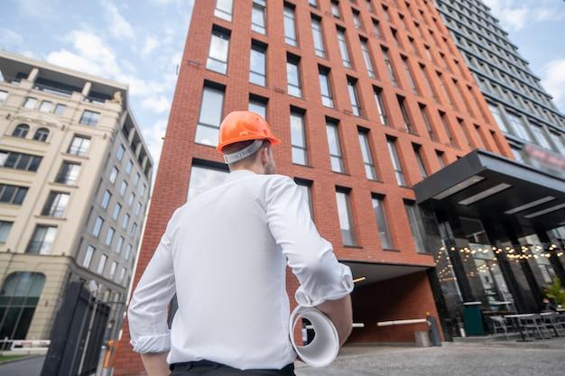 Мужчина-инженер в защитном шлеме стоит и смотрит на здание